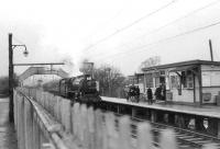 Hurlford shed's 45124 causes a stir amongst passengers on the platform at Williamwood awaiting their usual emu on a wet Saturday 11 April 1964. The Black 5 is on its way to Kings Park with a football special from Kilmarnock.<br><br>[John Robin&nbsp;11/04/1964]