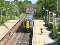 View east from the footbridge at Wallyford on 13 May 2014 as the 12.27 North Berwick - Edinburgh Waverley, formed by ScotRail unit 380105, arrives at the platform.<br><br>[John Furnevel&nbsp;13/05/2014]
