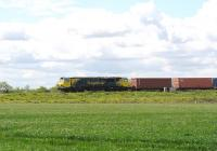 An eastbound container train on the Great Western main line passing the village of Bourton on the outskirts of Swindon on 13 May 2014. The locomotive is Freightliner 70009. <br><br>[Peter Todd&nbsp;13/05/2014]