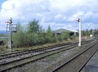 These shunting signals on the down side at Hellifield in April 2014 provide a contrast in styles - no prizes for guessing which one dates from the 21st century! Beyond is the bracket signal carrying the down starter and exit signal from the down loop.<br><br>[Bill Jamieson&nbsp;24/04/2014]
