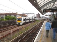 A train on the London - Tilbury - Southend line passing Shadwell DLR station on 26 May.<br><br>[John Thorn&nbsp;26/05/2014]