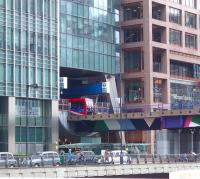 A DLR service about to leave Heron Quays station, squeezed between the various office buildings, on 26 May 2014.<br><br>[John Thorn&nbsp;26/05/2014]
