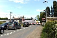 A southbound HST runs over the level crossing at Chevington, Northumberland (station closed 1958) on 17 May 2014.<br><br>[Peter Todd&nbsp;17/05/2014]