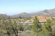 A very long container freight, with three locomotives at the head-end, on the Tehachapi Loop spiral in April 2014. Built by the Southern Pacific, the 19th century spiral is 0.73 miles of continious 2% grade.  Situated in the Tehachapi Pass in the California high desert, the arrangement enabled trains to ascend the pass between Mojave and Bakersfield.<br><br>[Brian Taylor&nbsp;15/04/2014]