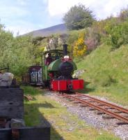 If only Cumbrian weather was always like this. <I>Sir Tom</I> makes light work of the gradient approaching the shed area at Threlkeld Quarry on 18 May. Notice the informal seating area to the left - an excellent place to eat lunch and watch the trains go by!<br><br>[Ken Strachan&nbsp;18/05/2014]