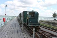 One of the UK's more unusual commuter lines, the Hythe Pier Tramway maintains a half hourly service to connect with the Southampton Ferry 363 days a year. One of the two 97 year old Brush 3rd rail electric locos is seen here approaching the station at the landward end of the pier on 25 May 2014.<br><br>[Mark Bartlett&nbsp;25/05/2014]
