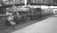 An otherwise quiet period at Carlisle station in August 1963 sees Upperby shed's Ivatt 2-6-0 no 46455 shunting a pair of TPO vans on the centre road.   <br><br>[K A Gray&nbsp;03/08/1963]