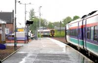 North and southbound ScotRail services meet at Larbert station in the pouring rain on 25 May 2005.<br><br>[John Furnevel&nbsp;25/05/2005]