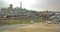 A panorama of Colchester station on a dismal 10th January 1976. The former Essex Hall Hospital (demolished 1989) occupies the background to the left while in the right foreground is the rough and ready overspill car park. Platform 2 in the station is hosting an unusual visitor in the form of a Class 33 at the head of a football special. It has just arrived with Crystal Palace fans who are about to transfer to the buses on the right and head for Colchester United's ground at Layer Road. The visitors went away happy despite the weather, having won three nil.<br><br>[Mark Dufton&nbsp;10/01/1976]