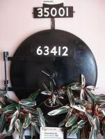 A smokebox door mocked up and purporting to be from Raven Q6 0-8-0 63412 adorns the wall of the entrance foyer of <I>The Sidings</I> Hotel and Restaurant adjacent to the ECML. The door displays a 52F Blyth shed plate, despite that loco being allocated to 51C West Hartlepool during its final years of service. The door, which is with hinges on the wrong side, appears to be from another class of loco, as the hinges do not match those in views of the class and there is not a pillar type protrusion on the centre line near the edge of the door on the opposite side to the hinges. <br><br>[David Pesterfield&nbsp;29/06/2014]