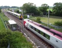 In the passing. London Midland and Virgin services pass at Gayton near Blisworth, Northants, in June 2014.<br><br>[John Steven&nbsp;24/06/2014]