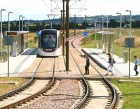 <I>'Oh ...ballast!!!'</I> Three fed up looking would-be passengers just miss a Sunday morning city bound Edinburgh tram leaving Ingliston Park and Ride on 13 July.<br><br>[John Furnevel&nbsp;13/07/2014]