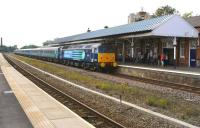 Locomotives and stock hired in from DRS by FTPE, forming a Liverpool - Scarborough service heading east at speed through platform 4 of Stalybridge station on 5 July 2014. The train consists of 47853 with a rake of DRS liveried Mark 2 coaches and 47841 on the rear.<br><br>[John McIntyre&nbsp;05/07/2014]