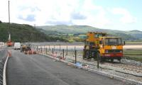 A road-rail vehicle parked on the realigned track alongside the newly widened road leading to the rebuilt Pont Briwet on 6th July 2014. The line from Harlech to Pwllheli is due to reopen by September 2014.<br><br>[Colin McDonald&nbsp;06/07/2014]