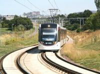Shortly after leaving Balgreen on a sunny 25 July a westbound Edinburgh tram climbs to cross the Edinburgh - Glasgow main line on the approach to the flyover at Saughton. <br><br>[John Furnevel&nbsp;25/07/2014]