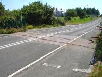 This well maintained level crossing is immediately north of the former Amlwch station site and runs across the A5025. It is on the section of line that continued to the former Associated Octel plant on the cliff top west of Amlwch Port. View east in July 2014.<br><br>[David Pesterfield 24/07/2014]