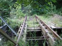 Looking north along the fenced off rail overbridge across the River Cefni, located a short distance from the former Llangefni station, showing the deteriorating condition of the rail supporting waybeams and missing section of base timber and sleepers.<br><br>[David Pesterfield&nbsp;23/07/2014]