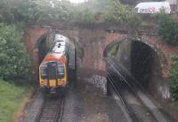 Pulling away from the Pokesdown stop in torrential rain on 23 May, 444023 on a Poole to Waterloo service passes through the twin arch bridge at the east end of the station. Thankfully, the station footbridge from which the photograph was taken has a full length roof.<br><br>[Mark Bartlett&nbsp;23/05/2014]
