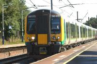 Clocking up the miles, London Midland 350374 helping out during the Commonwealth Games, strengthening the 1S71 Manchester Airport to Glasgow TPE service with a 350/4 on the rear. The train rushes north through Leyland on 2 August 2014.<br><br>[John McIntyre&nbsp;02/08/2014]