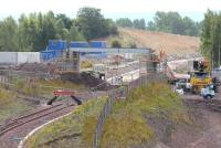 A new bridge being built over the Borders Railway route just beyond the turnback siding at Millerhill. The bridge will carry the road serving the recycling plant to be constructed on former railway land to the west of the current yard, with access from Whitehill Road. View south west towards Shawfair on 5 August 2014.<br><br>[John Furnevel&nbsp;05/08/2014]