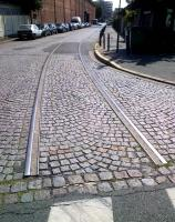 A disused industrial siding in the North Eastern Paris suburb of Pantin in August 2014. A turnout can just be seen in front of the approaching car. The cobblestones are laid out in an attractive pattern.<br><br>[Ken Strachan&nbsp;05/08/2014]