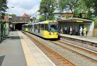Two Metrolink trams roll out of the 140yd Whitefield Tunnel and into the sunshine to call at Whitefield station on a service from Bury to Manchester and Altrincham. Just above the tunnel mouth is the old street level booking office from BR days. <br><br>[Mark Bartlett&nbsp;07/08/2014]