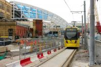 As the new roof at Manchester Victoria is installed by two huge cranes, Bury and Rochdale trams continue to pass on the temporary single line. Metrolink 3003 drops down from Shudehill to pass through the building site heading for Bury on 6th August 2014. <br><br>[Mark Bartlett&nbsp;07/08/2014]