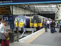 TransPennine Express 350401 prepares to depart platform 15 at Waverley with the 12.12 service to Manchester Airport. Standing alongside at platform 14 is ScotRail 334039 with the 12.21 service to Helensburgh Central.<br><br>[David Pesterfield&nbsp;/08/2014]