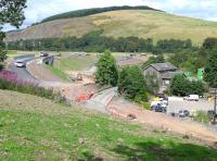 View east over the former level crossing at Fountainhall on 18 August, with the new access road well advanced to the left and the station house surrounded by the contractor's compound.<br><br>[Bill Roberton&nbsp;18/08/2014]