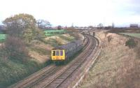 A Derby Class 108 DMU approaches Farington Curve Junction with a service from Ormskirk to Preston in 1978. At this time the former Preston to Liverpool main line was still double track as far as Midge Hall but singled not long after the picture was taken.  <br><br>[Mark Bartlett&nbsp;//1978]