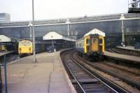 Looking back along the platform towards the buffers at London Waterloo station in March 1976 as 4-TC set no 433 departs past a class 74 electro-diesel with a parcels train. In the shadows on the left a class 08 and a class 33 can also be made out.<br><br>[John McIntyre&nbsp;19/03/1976]