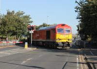 The morning commuter traffic is briefly halted on 27 August as DBS 60010 sets off across Strand Road in Preston with the bitumen empties returning to Lindsey refinery. A short distance beyond the crossing lies Fishergate Tunnel and the 1:29 climb back to the main line near Preston station. <br><br>[Mark Bartlett&nbsp;27/08/2014]