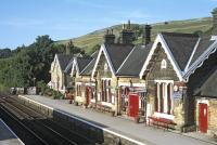 The up side station buildings at Settle, seen from the footbridge on the warm and sunny evening of 17 July 2014. The far building is the former stationmaster's house - this one  located rather closer to the railway than most of the other such houses on the S&C.<br><br>[Bill Jamieson&nbsp;17/07/2014]