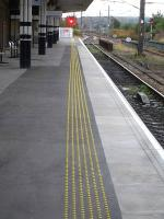 In a change from the small ribbed paving flag normally added to the rear of the platform coping flags, lines of yellow plastic studs, glued to the tarmac, have been used at Wakefield Westgate. Early morning view along the platform on 29 August 2014.<br><br>[David Pesterfield&nbsp;29/08/2014]