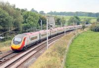 A London bound Pendolino hurries south through Grayrigg on 5 September. Immediately behind the train the points where the Up Loop rejoins the main line can be seen. Long closed Grayrigg station and the still used loops are behind the camera. Often photographed in steam days, Grayrigg station is now a mass of catenary and gantries surrounded by trees and no longer accessible. <br><br>[Mark Bartlett&nbsp;05/09/2014]