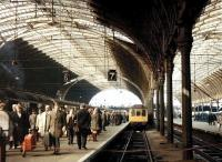 Saturday morning at Paddington on 29 March 1969. Passengers are heading for the concourse off a train from Plymouth which has recently arrived at platform 6 behind D1007 <I>Western Talisman</I>. Meantime, alongside at platform 7, a Reading line DMU stopping service is slowly approaching the buffer stops.<br><br>[John Furnevel&nbsp;29/03/1969]