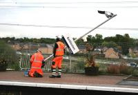 The last post. Final adjustments being made to the platform <I>furniture</I> at Baillieston on 1 October 2014. Part of the finishing touches in connection with the electrification of the Whifflet line. <br><br>[Colin McDonald&nbsp;01/10/2014]