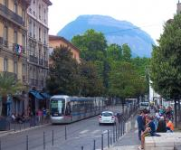 TAG Alstom Citadis 402 tram 6021 is one of a batch of 35 introduced to Grenoble in 2005. Here it is, dwarfed by a nearby Alp, and westward bound on a Line B service into Place Notre Dame in July 2014. It will  head into the city centre and on to its terminus at the Palais de Justice. This line is currently being extended into the north west of the city to serve the scientific community centred on the European Synchotron Radiation Facility.<br><br>[Andrew Wilson&nbsp;04/07/2014]