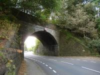Close up of the skew bridge on the former Holmfirth branch that crosses the A616 Sheffield to Huddersfield Road on the southern outskirts of Brockholes. View north in September 2014, showing the harshness of the curves facing road traffic. [See image 48869]<br><br>[David Pesterfield&nbsp;28/09/2014]