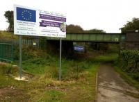A sign, a sign, give us a sign: the only evidence so far to be seen from road level, that a new station will shortly be built next to the Bermuda industrial park. The solum beneath the bridge is an abandoned branch from the Coventry canal. Nuneaton is to the left, Coventry to the right [see image 31064].<br><br>[Ken Strachan 12/10/2014]