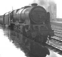 <I>'...and how was the weather in Blackpool?'</I> A returning summer Saturday holiday extra stands in the rain at Carlisle platform 1 on 17 August 1963. The train is the 10.35 ex-Blackpool Central, conveying through coaches for Perth and Edinburgh Princes Street. Royal Scot no 46128 <I>'The Lovat Scouts'</I> has just taken over the train which had arrived earlier behind Blackpool Central shed's Jubilee 45571 <I>South Africa</I>. [See image 39966]<br><br>[K A Gray&nbsp;17/08/1963]