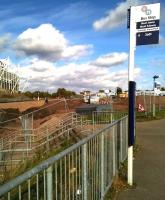 Mud, mud, glorious mud: a new railway station starts to take shape at last between Coventry's Ricoh Arena (left) and the popular Arena Retail Park (right). The steps lead down to a pedestrian underpass running below a three arch railway viaduct. View north towards Nuneaton on 19 October 2014. [See image 40050]<br><br>[Ken Strachan 19/10/2014]