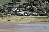 View from Portmeirion village across the Dwyryd estuary as the 1613 service to Machynlleth leaves Talsarnau on 10th October 2014.<br><br>[Colin McDonald&nbsp;10/10/2014]