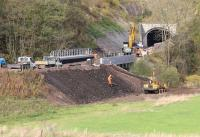 Activity around the south portal of Bowshank Tunnel on 24 October 2014 seen from alongside the A7. 'Slab track' has already been laid through the 200m tunnel (provided as 'passive provision' for possible future electrification). The double track route through the tunnel is part of a 6.4km dynamic passing loop on the new Borders Railway. [See image 49398]<br><br>[John Furnevel&nbsp;24/10/2014]