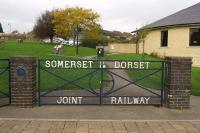 A set of gates at the entrance to 'The Railway Gardens' in Sturminster Newton in October 2014, with the name of the company which operated the railway. The blue plaque on the left gate post and placed there by the S&DJR Trust is inscribed <I<>Here once passed the engines and men of the Somerset & Dorset Joint Railway, Closed 7 March 1966</I>. <br><br>[John McIntyre&nbsp;22/10/2014]