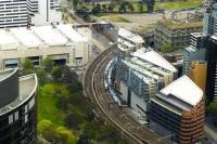 Two Metro emus passing on the 90 degree curve between Melbourne's Flinders Street Station (off to lower right) and Southern Cross (off to upper right). View from The Skydeck of the nearby Eureka Tower in October 2014.<br><br>[Colin Miller&nbsp;02/10/2014]