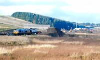Looking north towards Falahill village on 10 November 2014. On the left GBRf 66736+66752 continue their steady progress south with the tracklaying train. In the right background is the recently opened road bridge which now carries the realigned A7 over the new railway.   <br><br>[Ewan Crawford&nbsp;10/11/2014]