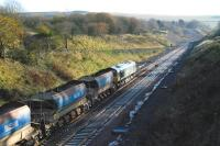 A low autumn sun casts shadows over the cutting at Tynehead on 10 November 2014, as Freightliner 66610 idles on the south end of a Borders Railway ballast train.<br><br>[Ewan Crawford&nbsp;10/11/2014]