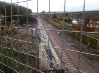 A relatively tidy looking Newtongrange station site on 25 November 2014, photographed looking south from the A7 overbridge. Platform construction looks well advanced and a noise barrier has been erected between the new railway and the gardens of Jenks Loan. Work is in progress on the main entrance and car park off to the left.  <br><br>[John Yellowlees&nbsp;25/11/2014]
