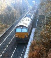 A pair of class 66 locomotives with a ballast train on the Edinburgh <I>sub</I> on a bright Sunday morning in October 2003. The train is about to pass north through the abandoned platforms of the former Craiglockhart station with EWS 66050 leading.<br><br>[John Furnevel&nbsp;06/10/2003]